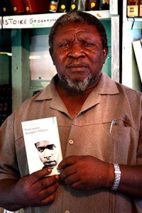 "Antoine Lamoraille is a scholar, public figure, community leader, and one of the founders of Mama Bobi. He insisted to be pictured with one of his books of reference: ""Black Skins, White Masks"" by Franz Fanon.  Antoine Lamoraille est un érudit, une figure publique, un chef et un des fondateurs de l'association Mama Bobi. Il a tenu pour se faire photographier avec un de ses ouvrages de référence: ""Peaux Noires, Masques Blancs"" par Franz Fanon."